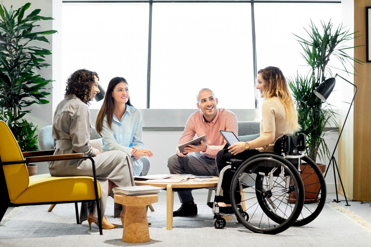 Disabled businesswoman discussing with colleagues. Male and female professionals planning in business meeting. They are sitting at office.